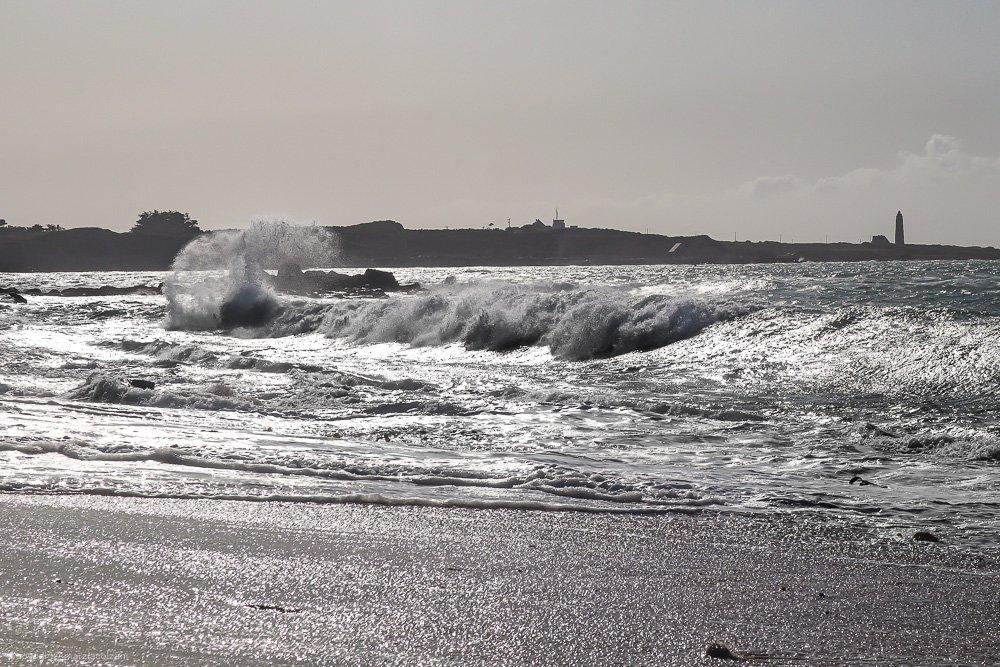 onde spumeggianti si infrangono su una grande spiaggia al tramonto