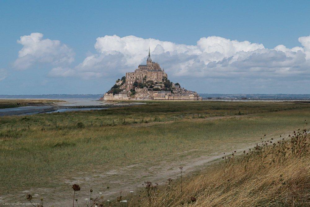 vista di Le Mont St Michel con il mare ritirato di giorno che sistaglia nel cielo blu con nuvole bianche in mezzo al prato sferzato dal vento maestosa rocca in mezzo al mare