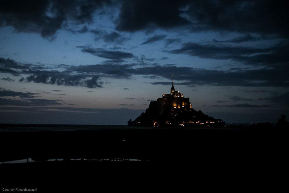vista nottura di mont st michel circondato dalla marea cielo blu notte e ombre nere e le stupende luci dorate della rocca illuminata per la notte