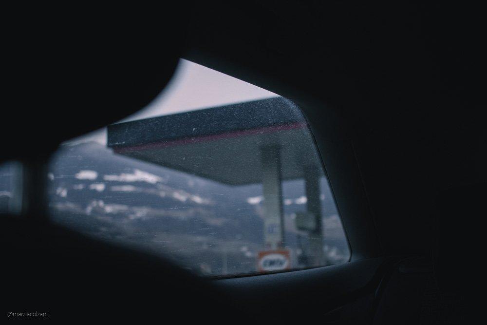 finestrino posteriore di un'auto che mostra una stazione di servizio colori freddi è inverno