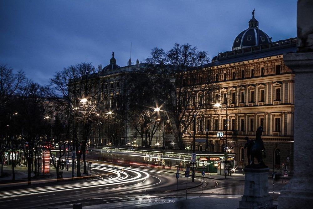scatto fotografico notturno effettuato con la tecnica della lunga esposizione e light painting siamo in centro a Vienna e si vedono edifici storici e una strada trafficata con le luci dei lampioni a creare piccole stelle e scie di luce bianche e rosse che sono i fanali delle auto