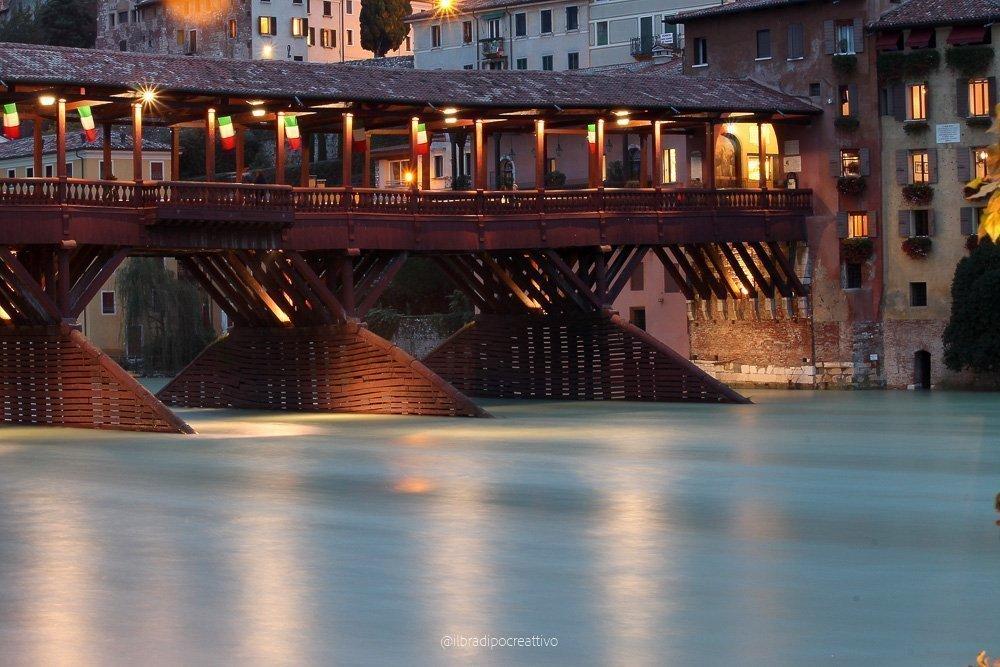 fotografia effettuata con lunga esposizione sul ponte vecchio di bassano del grappa pieno di piccole bandiere italiane, è sera e le luci dorate sono accese alle finestre e sul ponte, si vede il fiume brenta e il colore dell'acqua è smeraldo e sembra seta