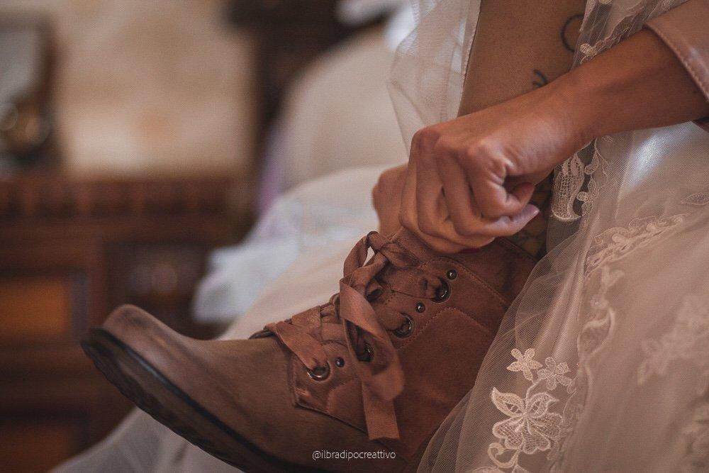 la mano di una donna che si sta infilando uno scarponcino in primo piano, lei è vestita da sposa e lo scarponcino è di un intenso color rosa cipria sullo sfondo sfocato un comodino e il letto in cui è seduta