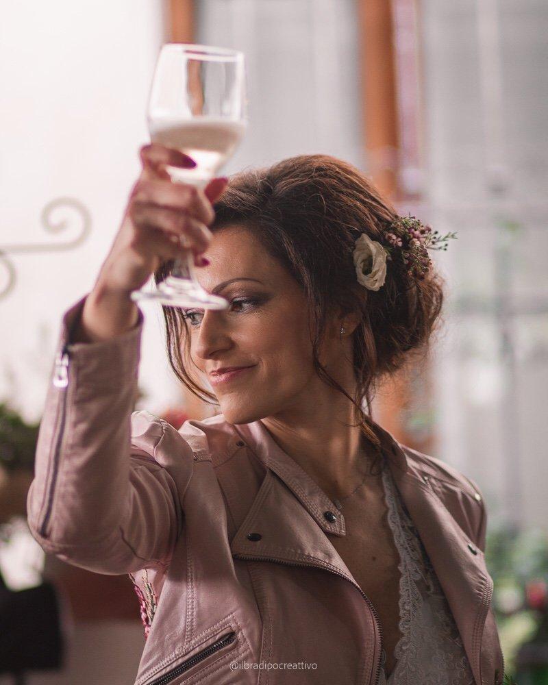una donna in primo piano vestita da sposa, capelli raccolti e fiori tra i capelli, sorride con uno sguardo doolce mentre solleva un calice di vino bianco, si intravede il vestito di pizzo solo ad un giubbetto in ecopelle rosa