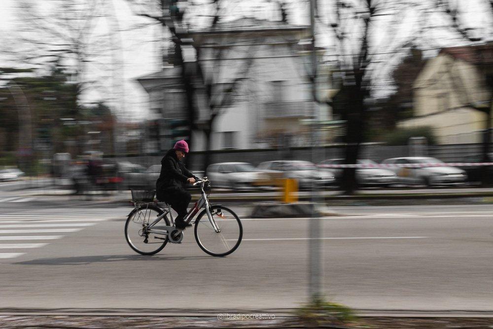 una donna in bicicletta con un cappello viola, la fotografia è stata scattata lungo un viale alberato e presenta tutto il contorno mosso tranne la donna e la bici che sono perfettamente a fuoco e fermi all'interno del fotogramma