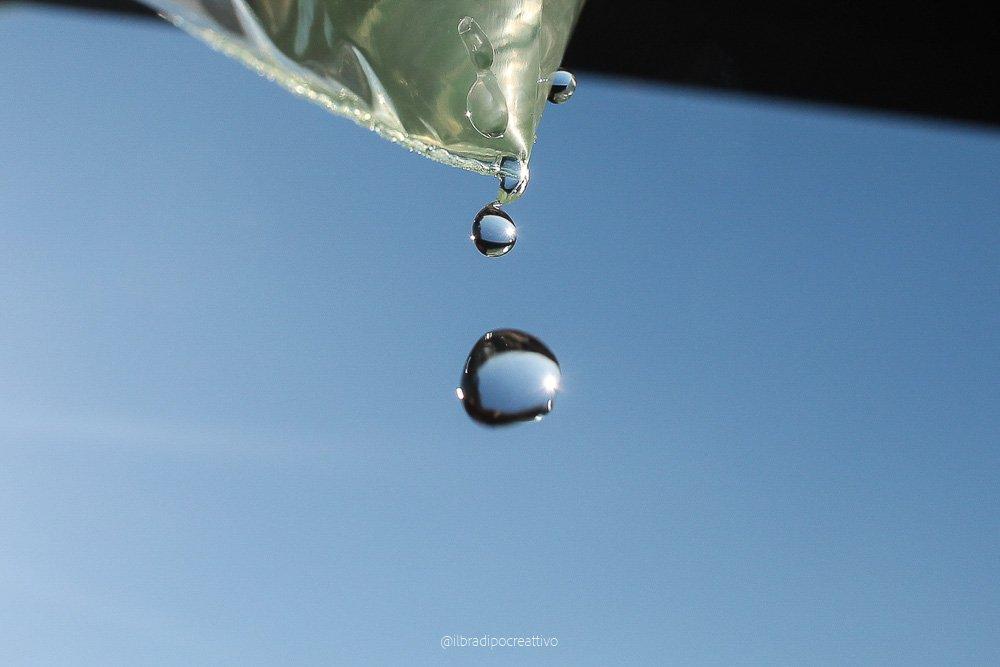 fotografia di gocce d'acqua perfettamente ferme e sospese nel cielo blu si intravede una piccola porzione di qualcosa di verde dal quale escono le gocce