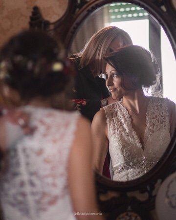 una donna vestita da sopa vista di spalle e contemporaneamente vista di fronte riflessa allo specchio mentre guarda alla sua sinistra mentre la testimone la aiuta a sistemare il vestito da sposa di pizzo bianco da dietro una luce romantica dalla finestra