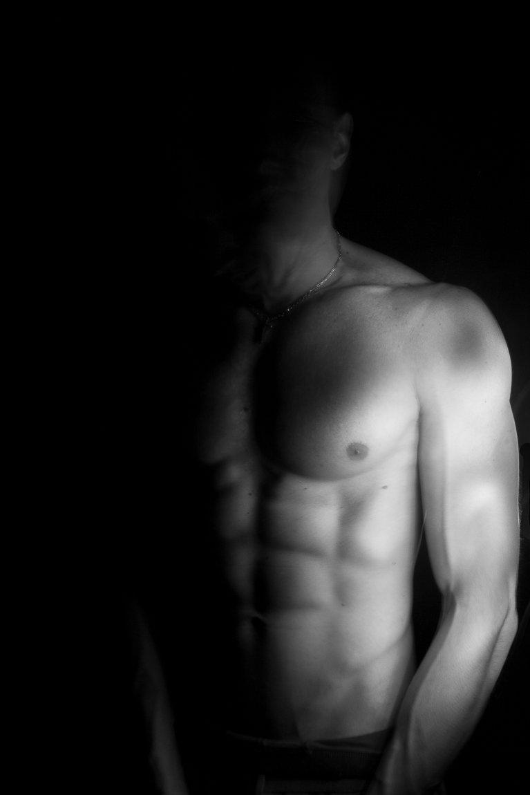 immagine che utilizza la tecnica del light paintin in cui si vede il petto di un uomo nudo illuminato solo parzialmente tanto da far risaltare i muscoli forti delle braccia e gli addominali