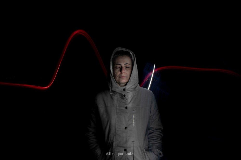 foto nottura con una donna vestita con cappuccio illuminata da una luce bianca e dietro nel buio una striscia rossa che simula il battito cardiaco, tecnica fotografica del light painting foto firmata ilbradipocreattivo