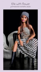 servizio fotografico di moda alle barbie seduta su una sedie con un vestito un cappellino e degli stivali neri, con un fiore bianco di magnolia sullo sfondo,nero in una posizione da vera modella fashion