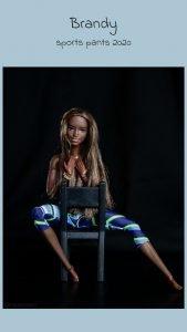 servizio fotografico di moda alle barbie con un paio di pantaloni sportivi seduta su una sedia messa al contrario, si copre il petto scoperto con i capelli e con le mani, sfondo nero e posa da vera modella fashion