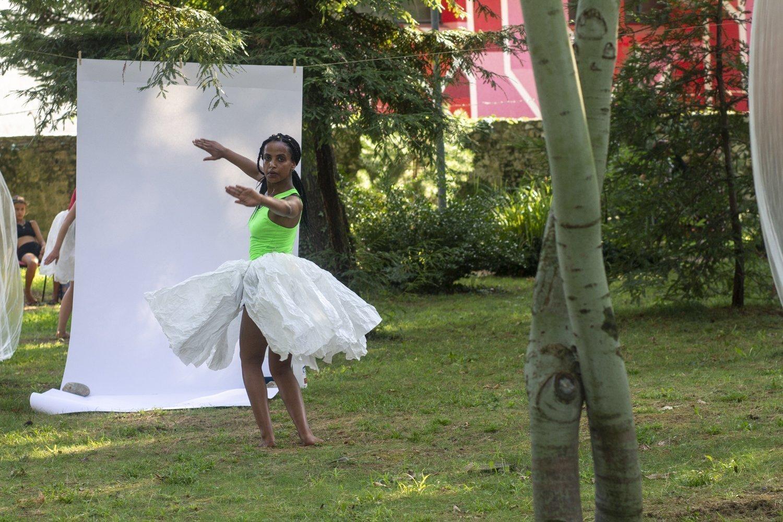 ballerina di colore con un fondale bianco e un tutù di carta bianca che danza in un boschetto