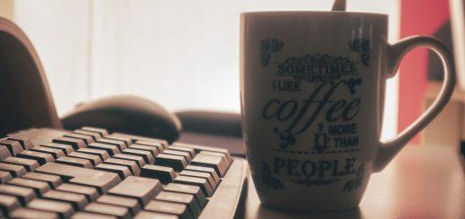 tastiera di un computer nera su una scrivania bianca, sullo sfondo una luce calda e una grande tazza di caffè con scritto spesso preferisco il caffè alle persone ambientazione calda e intima
