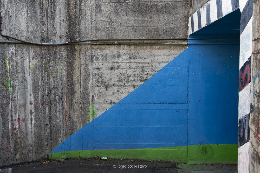 foto di un sottopassaggio in cemento con dei colori sgargianti blu che creano un triangolo